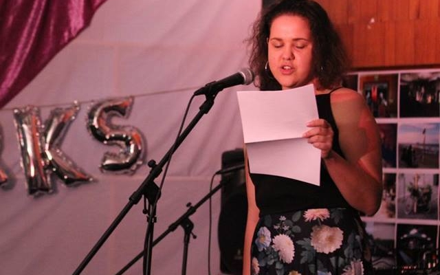 A person reading at a microphone.