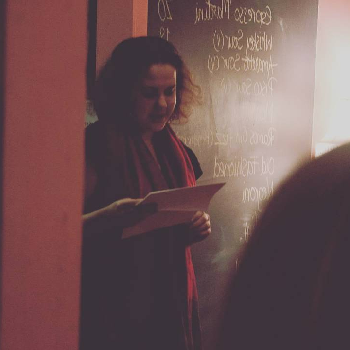 A person reading poetry in a dimly-lit room.