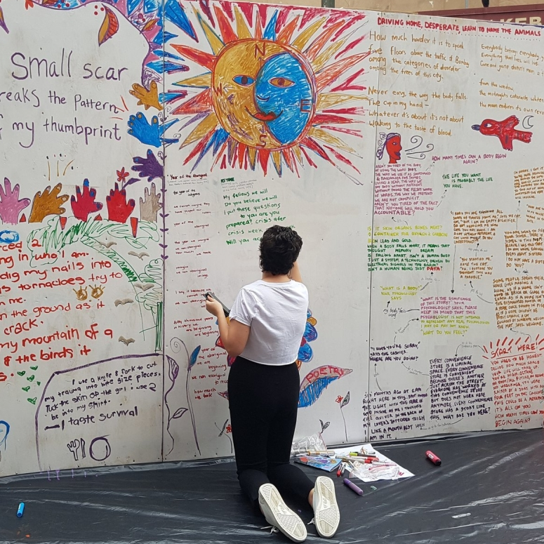 A person writing poetry on a pop-up wall.